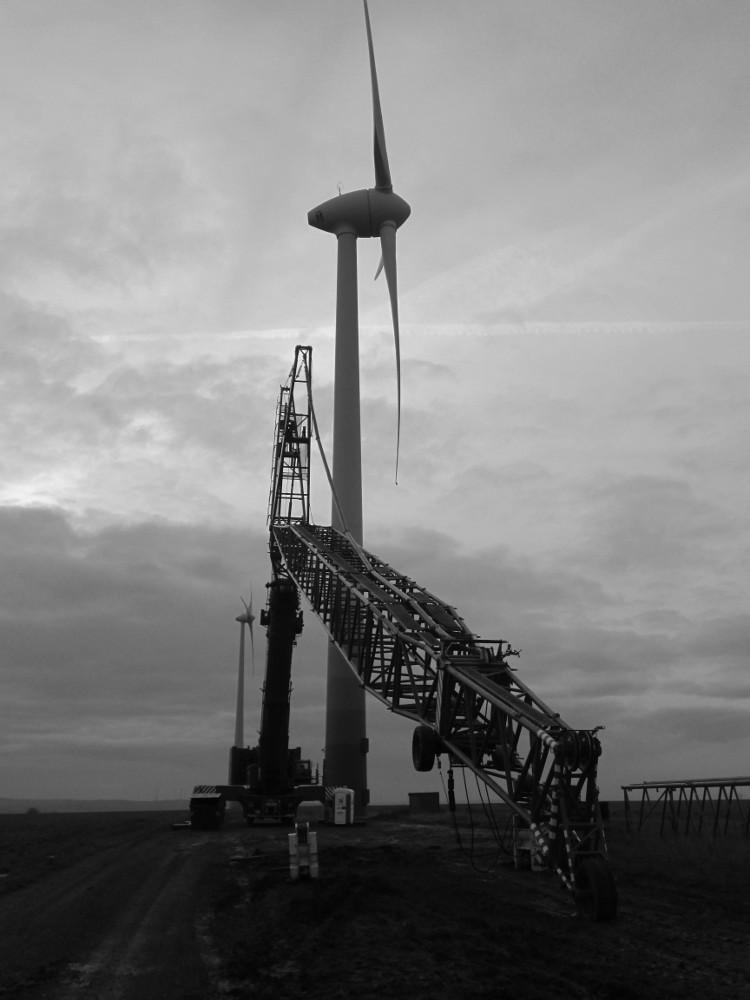 """Das s/w-Foto zeigt einen """"ruhenden"""" KRan an einer Windkraftanlage, der Kran ist so zuammengeklappt, dass die Spitze auf dem Boden liegt."""