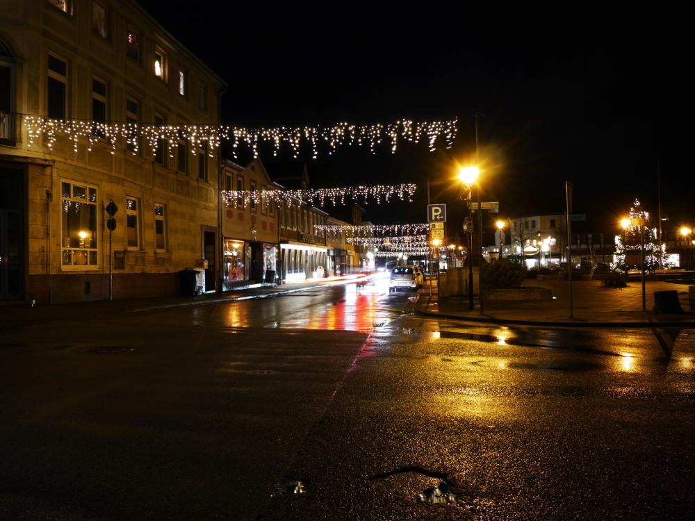 Ds Foto zeigt eine Straßenszene bei Dunkelheit, über die Straße sind leuchtende Weihnachts-Netze gespannt.
