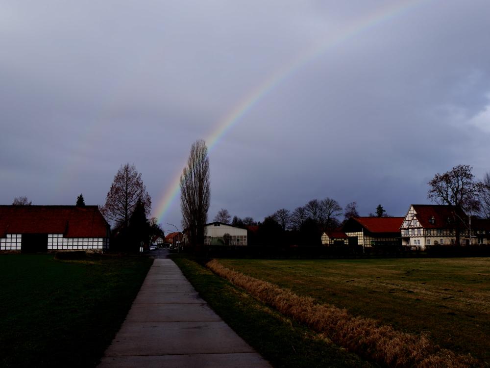 Das Bild zeigt einen Regenbogen, der ungefähr an einem Haus in Verlängerung eines Feldwegs beginnt und nach rechts weg geht.