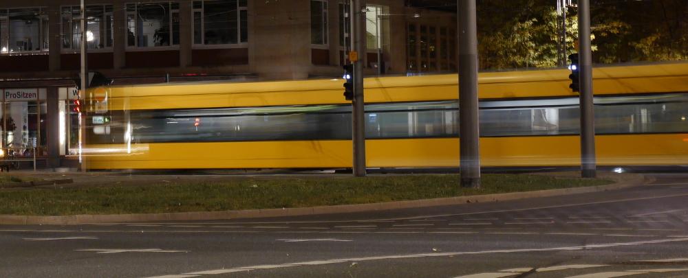 Das Foto zeigt eine fahrende, gelbe Straßenbahn. Es ist eine leichte Langzeitbelichtung, so dass man die Bewegung im Bild erkennen kann.