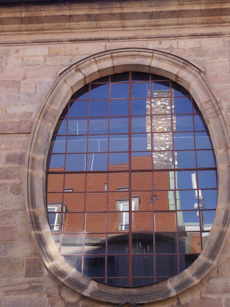 Das Foto zeigt ein ovales Kirchenfenster, welches aus vielen kleinen Scheiben besteht. In den Scheiben spiegelt sich das gegenüberliebende Haus, dessen Schornstein und daneben ein Mobilfunk-Mast