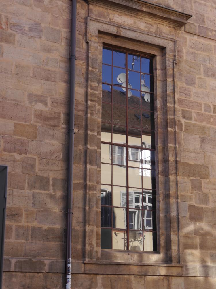 Das Foto zeigt ein ovales Kirchenfenster, welches aus vielen kleinen Scheiben besteht. In den Scheiben spiegelt sich das gegenüberliebende Haus und die Parabolantennen auf dessen Dach
