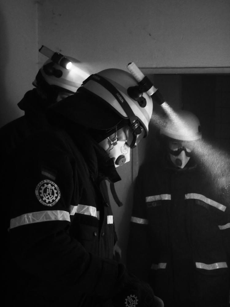 Das s/w-Foto zeigt 3 THW-Helfer bei einer Übung, sie tragen Einsatzanzug, Helm, Schutzbrille und Staubmasken. Im Staub kann man die Lichtkegel der Helmlampen erkennen.