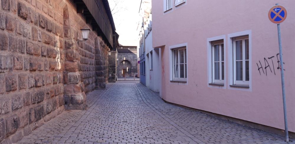 """Das Foto zeigt eine kleine gepflasterte Gasse an der Nürnberger Stadtmauer. Die historische Stadtmauer ist links, rechts stehen Gebäude. Das erste Gebäude hat eine rosa Fassade, etwa in Höhe eines Haltverbotschildes wurde mit schwarzem Stift das Wort """"Hate"""" auf die Fassade geschrieben, man kann weitere Garffittis erahnen."""