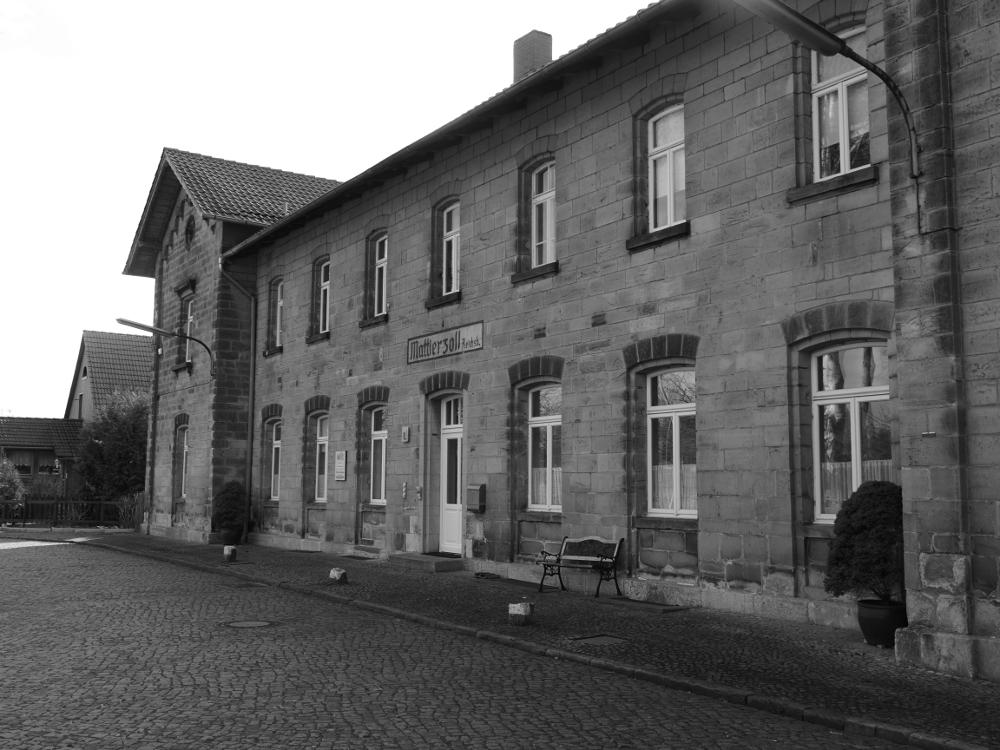 """Das alte Bahnhofsgebäude von Mattierzoll. Es ist aus massivem Stein, über der Eingangstür kann man die Inschrift """"Mattierzoll"""" und klein """"Reichsb."""" erkennen."""