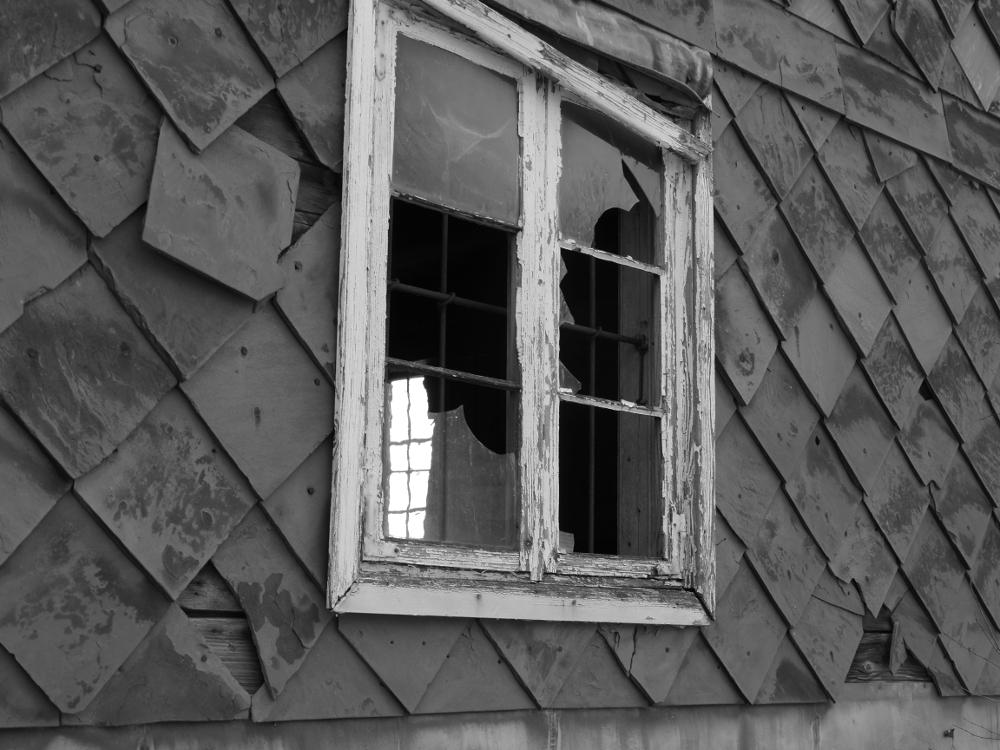 Ein Fenster mit zerbrochenem Scheiben an einer Wand aus beschädigten Schieferplatten.