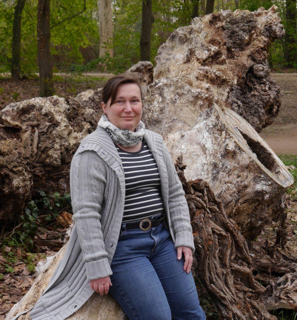 Dasa Foto zeigt eine Frau in grauer Strickjacke, die sich gegen die Wurzel eines umgestürzten Baums lehnt.