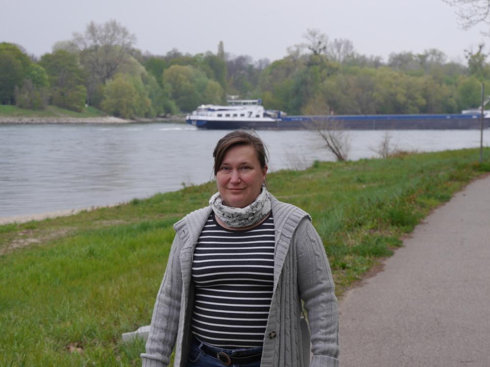 Dasa Foto zeigt eine Frau in grauer Strickjacke, im Hintergrund ist der Rhein und auf diesem ein Binnenschiff