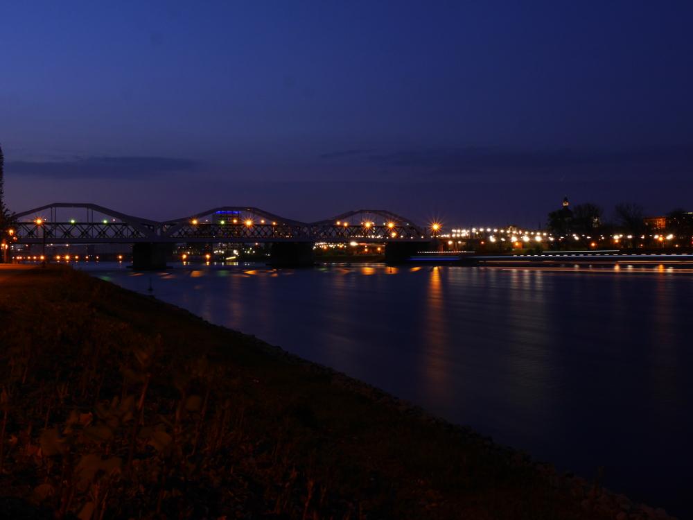 Nachtfoto der Rheinbrücke zwischen Ludwigshafen und Mannheim, auf der rechten Seite sieht man die Striche von den Lichtern von Schiffen auf dem Rhein.