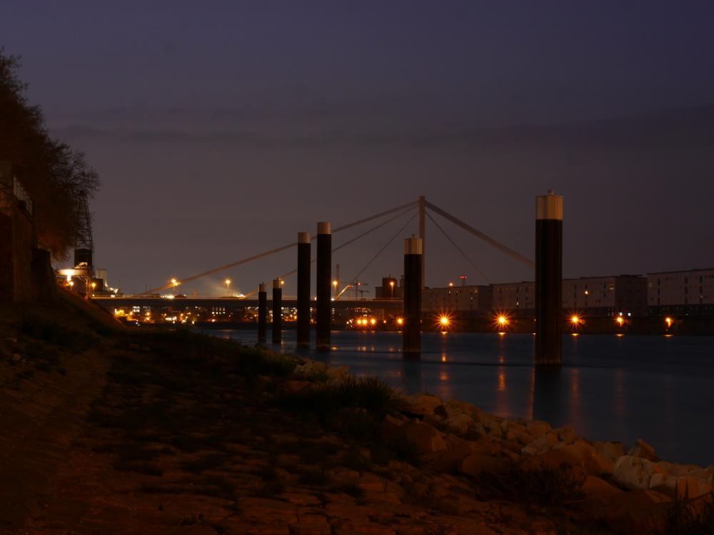 Nachtfoto der Rheinbrücke zwischen Ludwigshafen und Mannheim, ziemlich zentral sieht man grosse Pfosten zum festmachen von Schiffen, im Hintergrund schon die ersten Teile des BASF-Werks