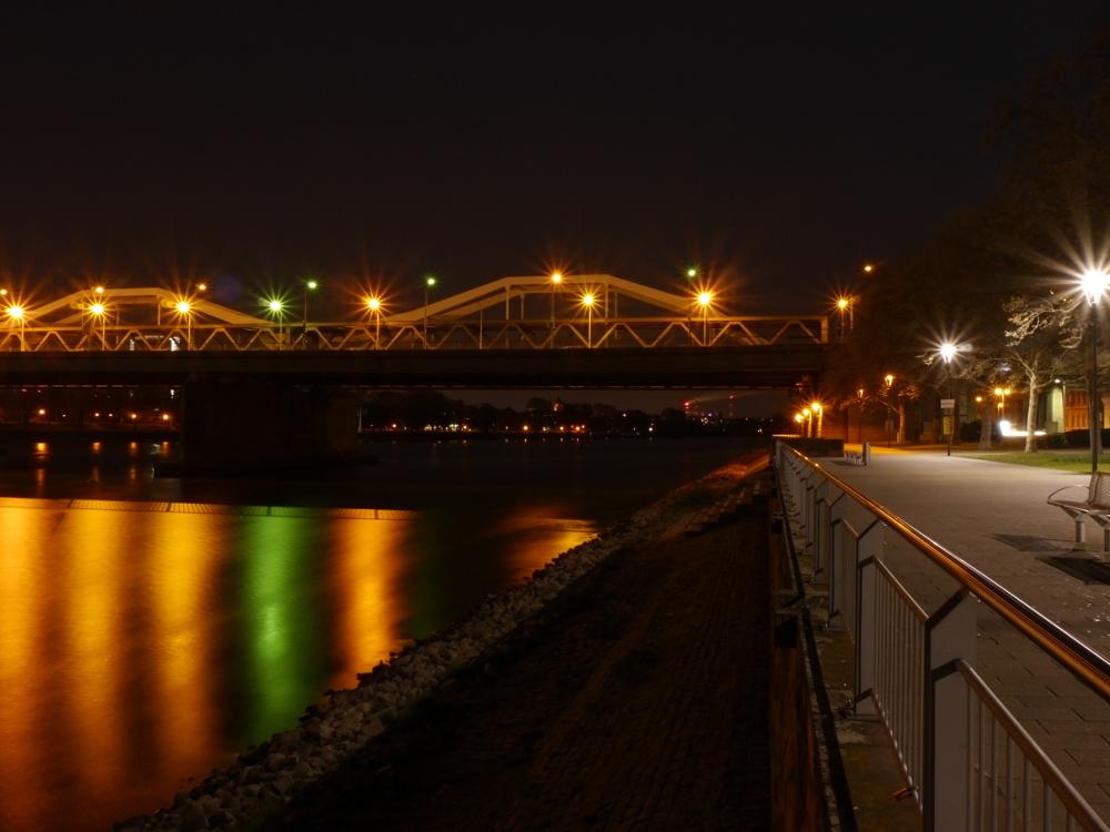 Nachtfoto von einem Teil der Rheinbrücke zwischen Ludwigshafen und Mannheim, die Strassenlaternen reflektieren sich gelb und grün im Rhein.