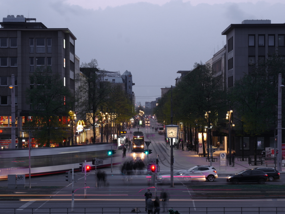 Eine Langzeitaufnahme der Mannheimer Planken am frühen Abend, durch die lange Belichtungszeit sind einige Autos/Strassenbahnen/Menschen verwischt.