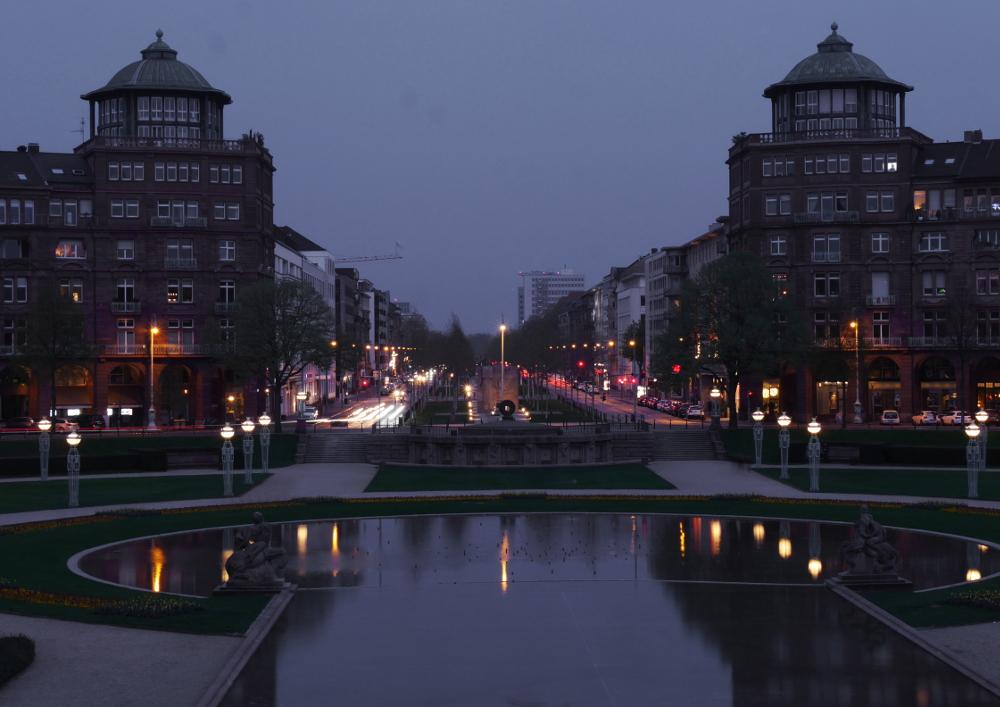 Eine Aufnahme der Mannheimer Augustaanlage vom Wasserturm auf, es war schon eine Langzeitaufnahme, einige Autos sind zu Stricken geworden. Ein Teil der Lampen reflektieren sich im Teich.