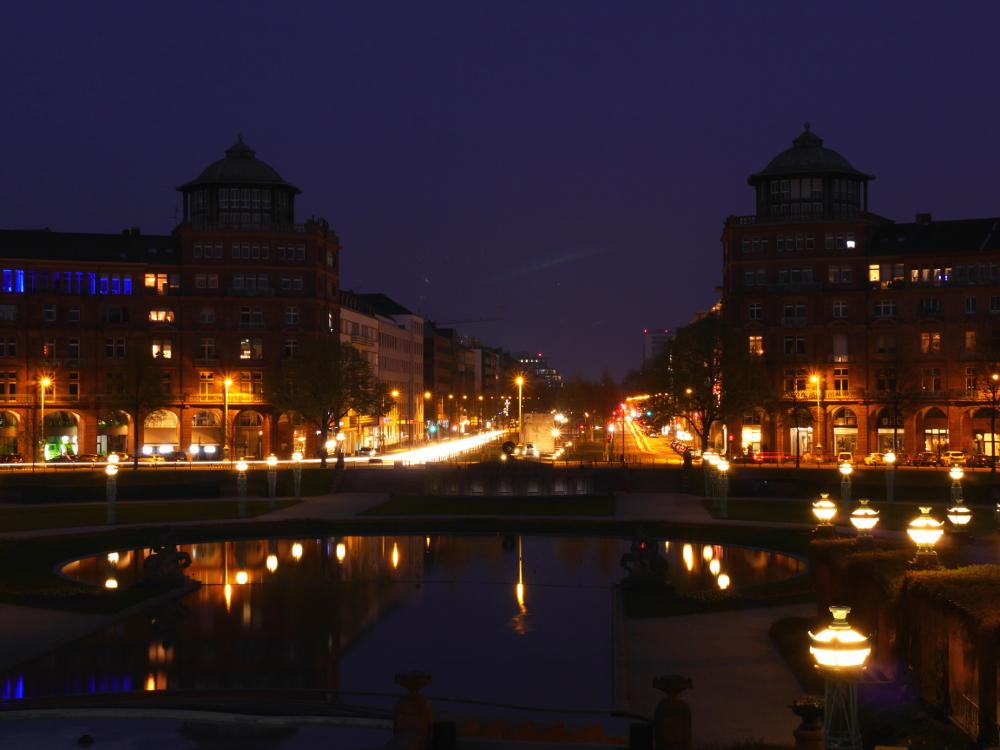 Eine Nachtaufnahme der Augustaanlage in Mannheim, die Lichter refklektieren sich im Teich und die Scheinwerfer der Autos bilden Streifen.