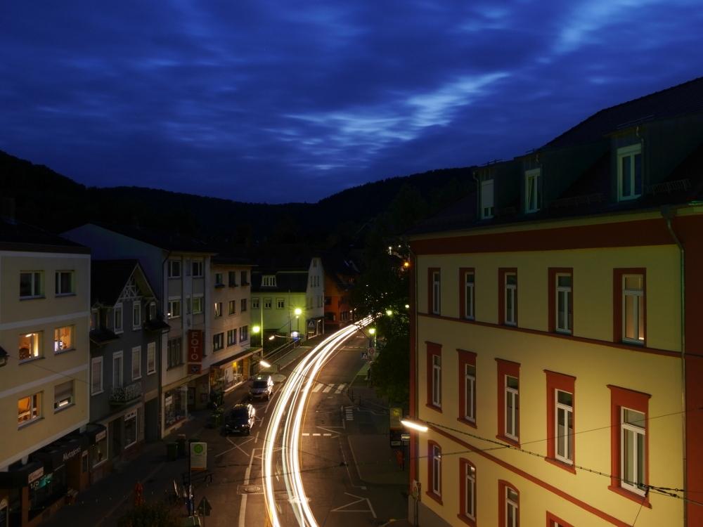 Das Foto zeigt eine Straßenszene nach Sonnenuntergang, es ist schon dunkel. Die Lichter der Autos sind als Streifen auf der Straße, rechts und links der Straße stehen Häuser