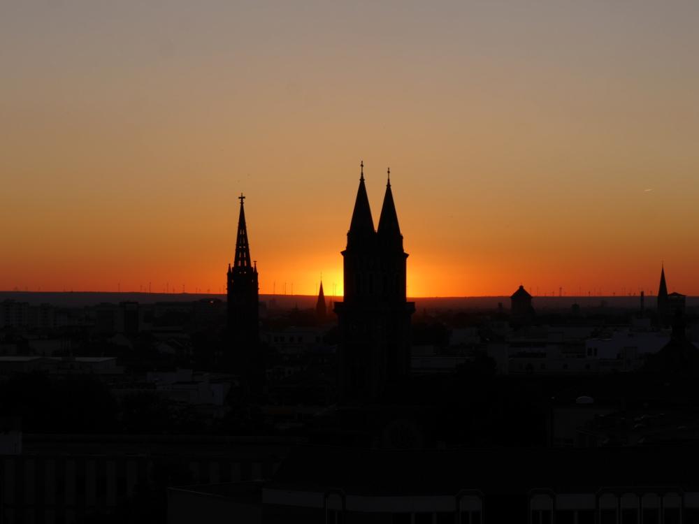 Das Foto zeigt einen Sonnenuntergang, die Sonne steht genau zwischen zwei Kirchtürmen, die die anderen Gebäude überragen