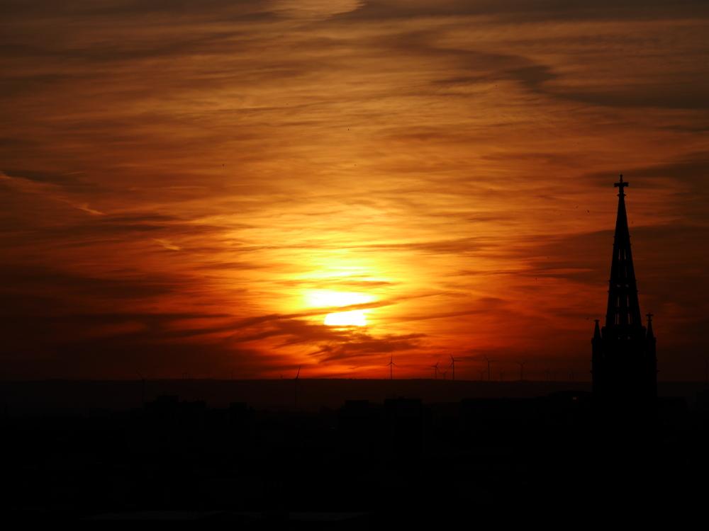 Das Foto zeigt einen Sonnenuntergang, durch die Wolken wirkt es, als wenn der Himmel brennt. Im Hintergrund sieht man Windkraftanlagen, rechts einen Kirchturm