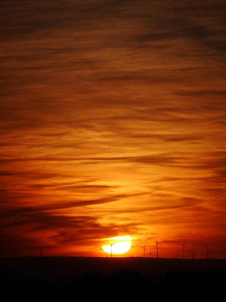 Das Foto zeigt einen Sonnenuntergang, die Sonnenscheibe berührt fast die Erde. Man sieht ein paar Windkraftanlagen