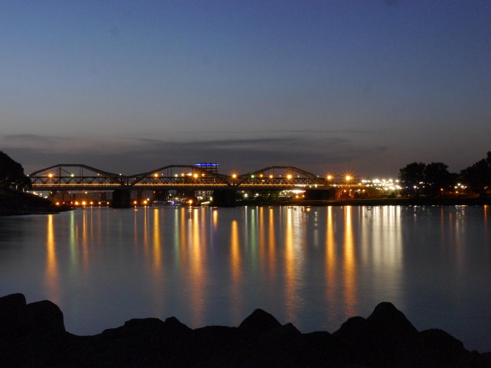 Das Foto zeigt eine Bogenbrücke über den Rhein bei Nacht, man sieht wie sich die Lichter im Rhein spiegeln.