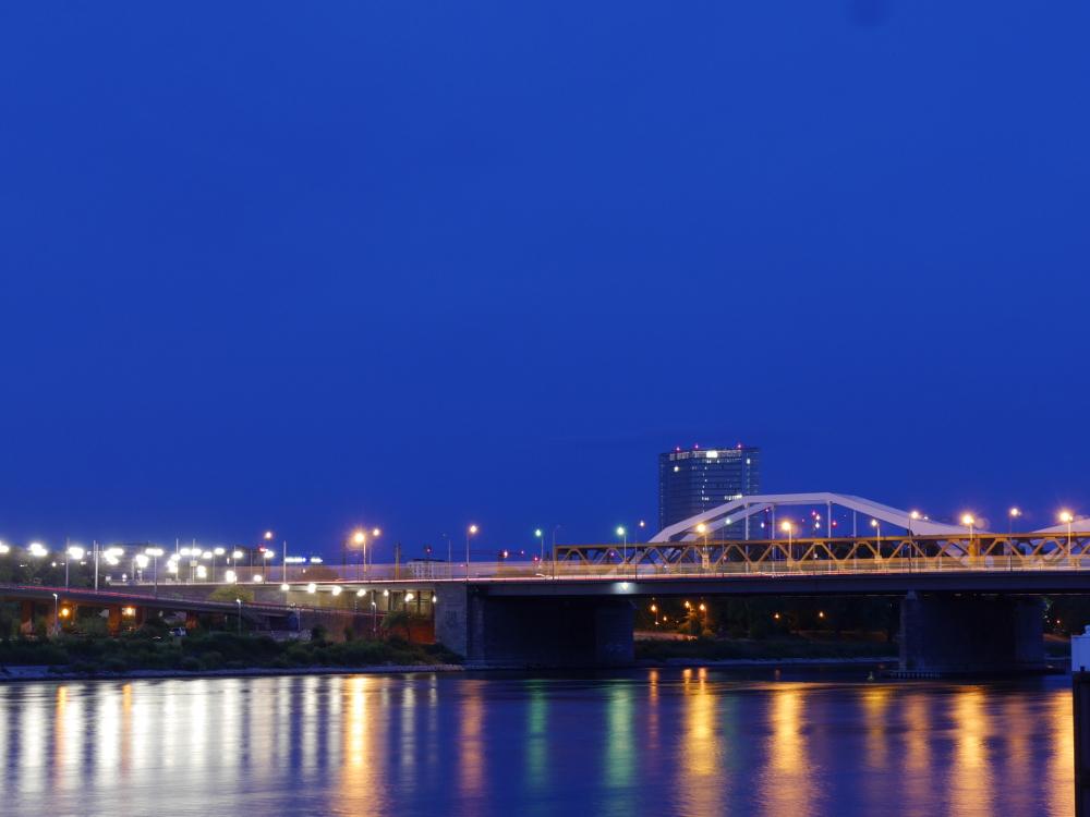 Das Foto zeigt eine Bogenbrücke über den Rhein nach Sonnenuntergang, man sieht wie sich die Lichter im Rhein spiegeln.