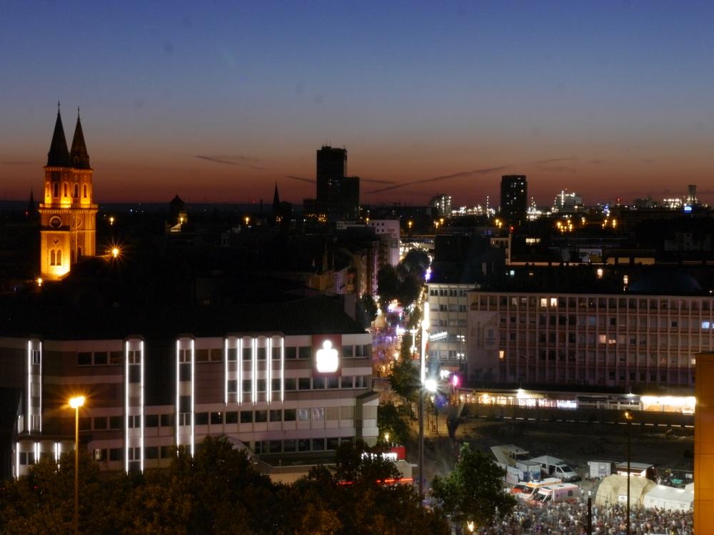 Das Foto ist eine Nachtaufnahme aus Ludwigshafen, man sieht erleuhtete Gebäude, eine beleuchtete Straße die vom Fotografen weg führt sowie Einsatzfahrzeuge des Roten Kreuzes und viele Menschen, die zu einer Bühne gehen.