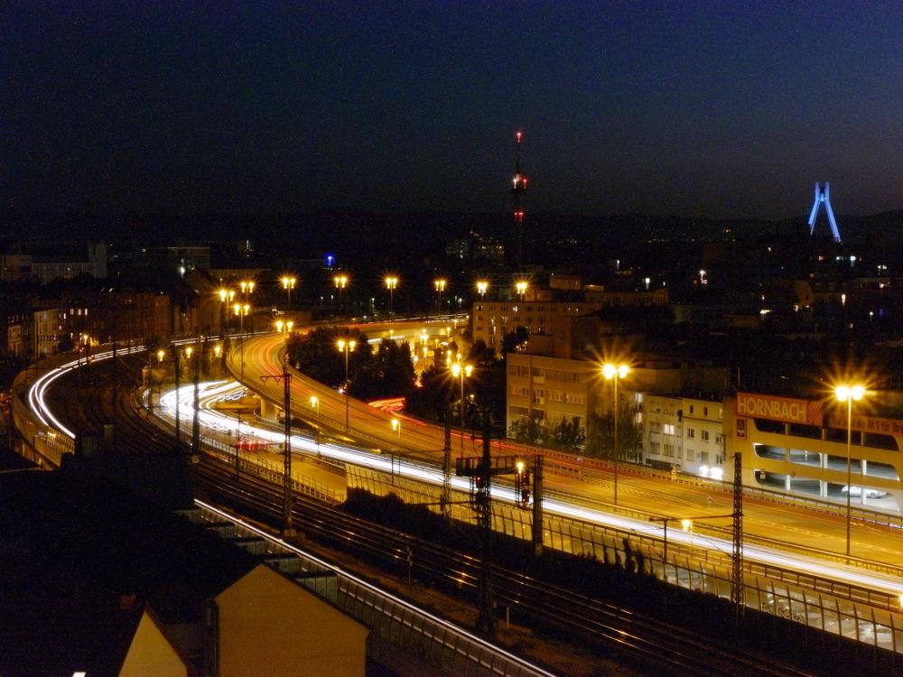 Nachtaufnahme von Straßen und Schienen, die in einer Kurve weitergehen. Durch die Lange Belichtungszeit sind die Scheinwerfer der Fahrzeuge nur als Streifen erkennbar.