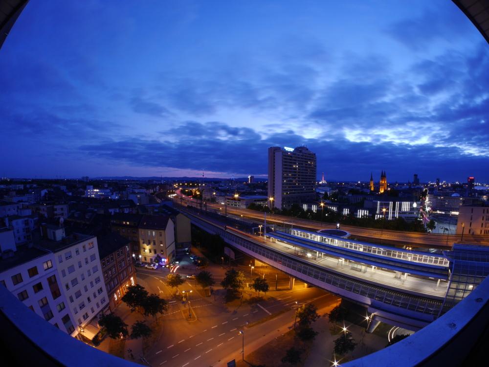 """Das Foto ist eine verzerrte Fischaugen-Aufnahme, es zeigt das nächtliche Ludwigshafen wührend der """"blauen Stunde"""". Man kann die Züge und Fahrzeuge nur durch die Streifen ihrer Lichter erkennen."""