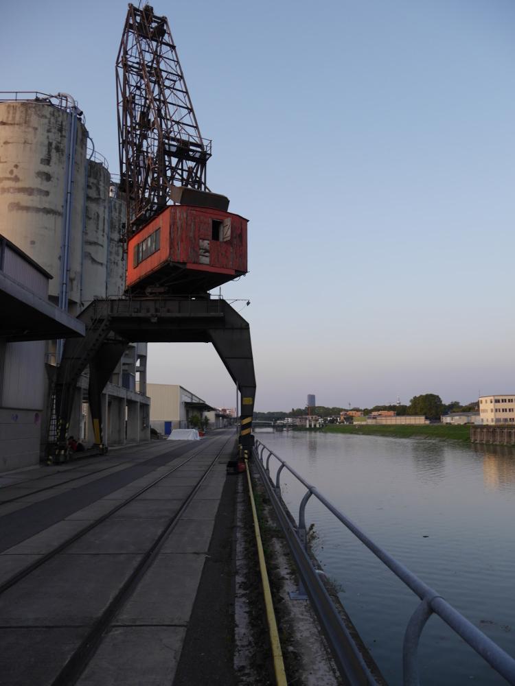 Das Bild zeigt einen Drehkran im Luitpoldhafen in Ludwigshafen, der Kran steht erhöht, unter ihm gehen zwei Bahngleise durch.