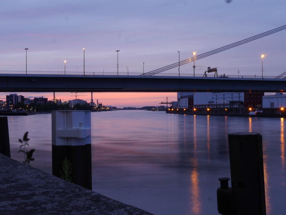 Das Bild zeigt einen Blick unter die Kurt-Schmacher-Brücke in Ludwigshafen am Abend, Links das Industriegelände der BASF, Rechts Mannheim