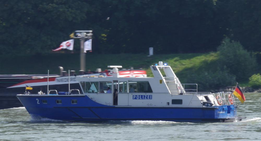 Dasa Foto zeigt ein Boot der Wasserschutzpolizei auf dem Rhein, es fährt gerade mit Blaulicht an einem Frachtschiff vorbei.