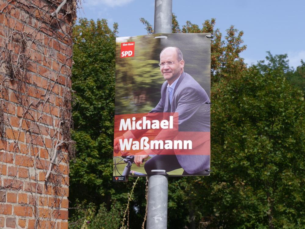 Das Foto zeigt den Bürgermeister-Kandidaten Michael Waßmann auf einem Werbeplakat auf dem Fahrrad