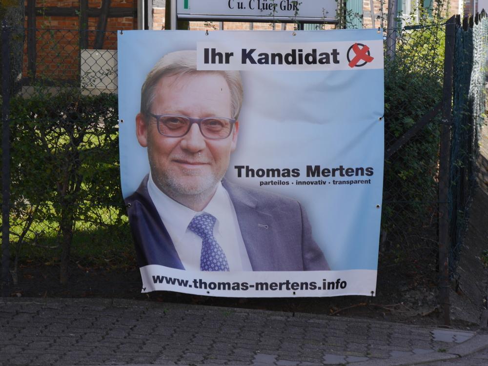 Das Foto zeigt ein Werbeplakat des Bürgermeister-Kandidaten Thomas Mertens inkl. Angabe der Homepage.