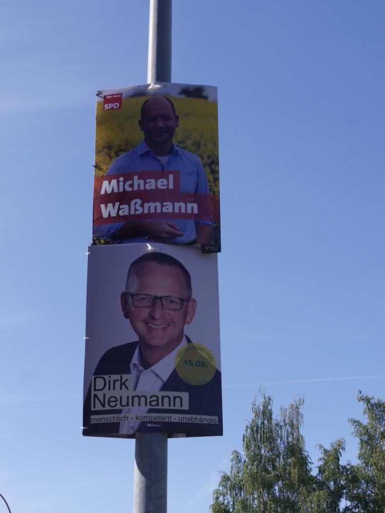 Das Foto zeigt die Plakate der Bürgermeister-Kandidaten Michael Waßmann und Dirk Neumann übereinander an einer Laterne