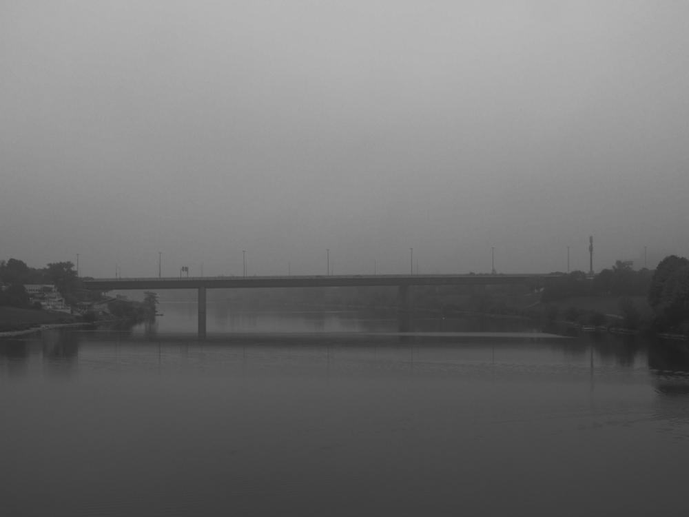 Das s/w-Foto zeigt eine Brücke über die Donau, die im Nebel verschwindet.