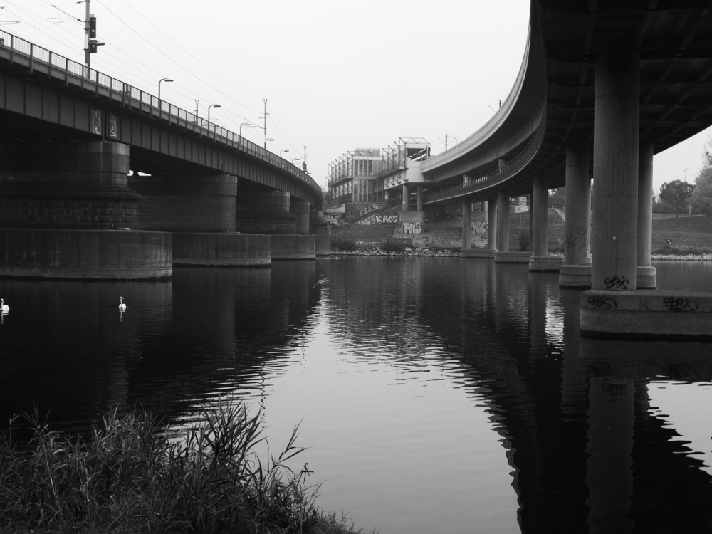 Ein Blick über die neue Donau zwischen zwei Bahnbrücken, im Hintergrund sieht man die Station