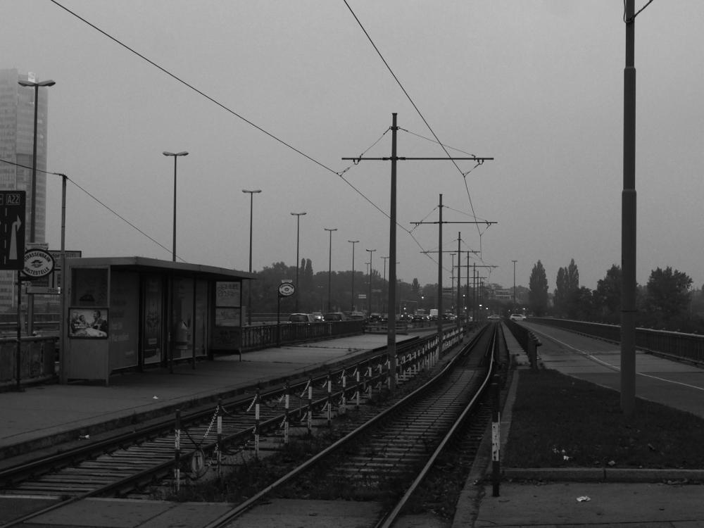 Das s/w-Foto zeigt einen Blick auf einer Brücke über die Neue Donau, der Fotograf steht an den Straßenbahngleisen.