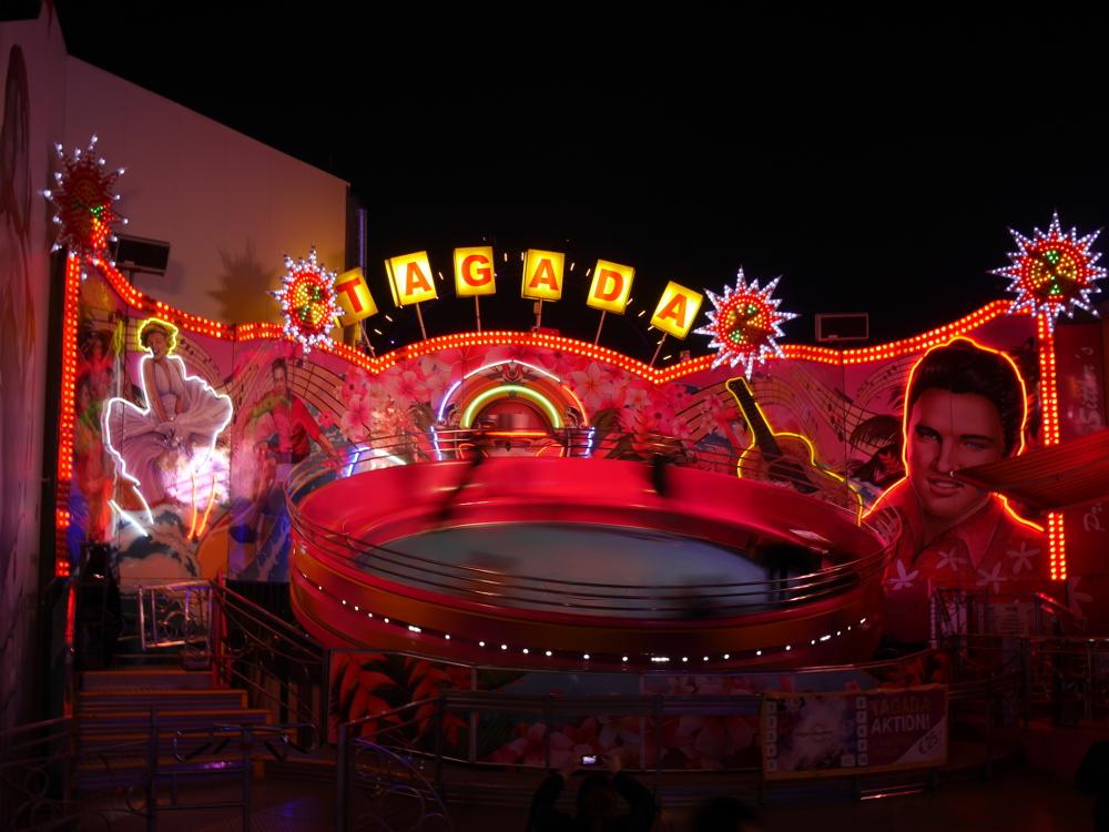 Das Foto zeigt ein beleuchtetes Fahrgeschäft, welches aus einer sich schnell rotierenden, geneigten Scheibe besteht.