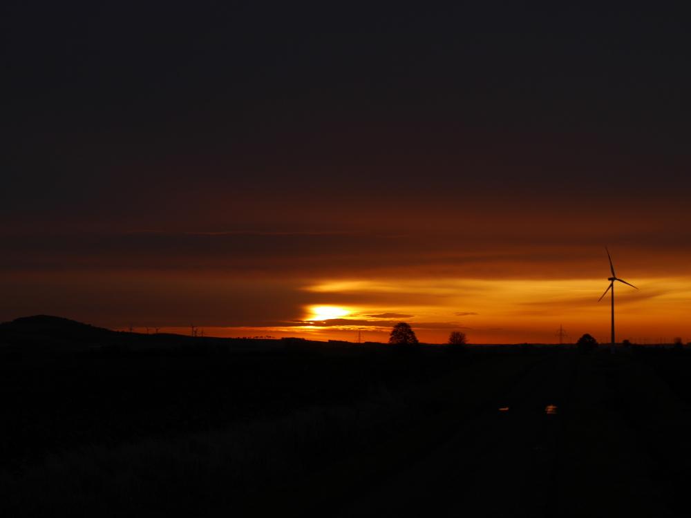 Das Foto zeigt einen Sonnenaufgang, links ist die Erhebung des Hesebergs, rechts sieht man ein Windrad, in der Landschaft sind kaum sichtbar weitere Windräder und der Fotograf steht auf einem dunklen Feldweg....