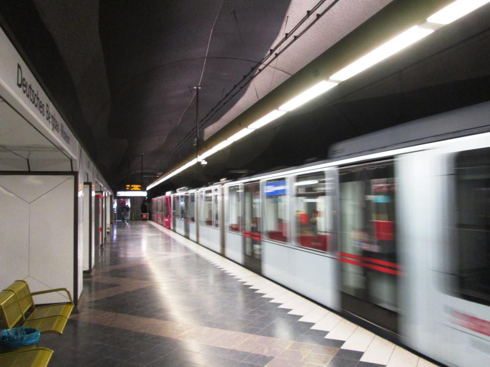 """Das Foto zeigt eine U-Bahn-Station, auf der linken Seite ist der Stationsname """"Deutsches Bergbau-Museum"""" zu lesen, rechts sieht man eine ausfahrende U-Bahn, welche durch die lange Belichtungszeit verzerrt ist."""