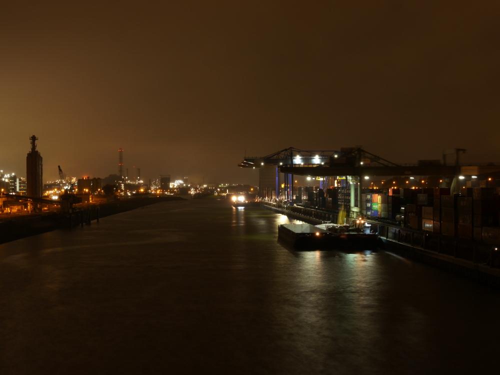 Das Foto zeigt die Nachtaufnahme einer Hafenszene, rechts ist die Containerverladung mit Kranen, links ein hell erleuchtetes Industriegebiet, dazwischen das Hafenbecken