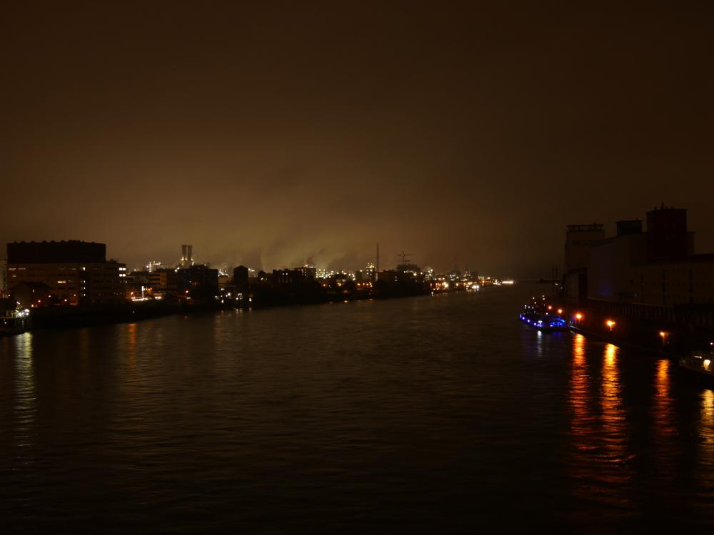 Eine Nachtszene am Rhein zwischen Mannheim und Ludwigshafen, links die hell erleuchteten Industriebetriebe der BASF, Rechts eher dunkle Lagerhallen, dazwischen der Rhein