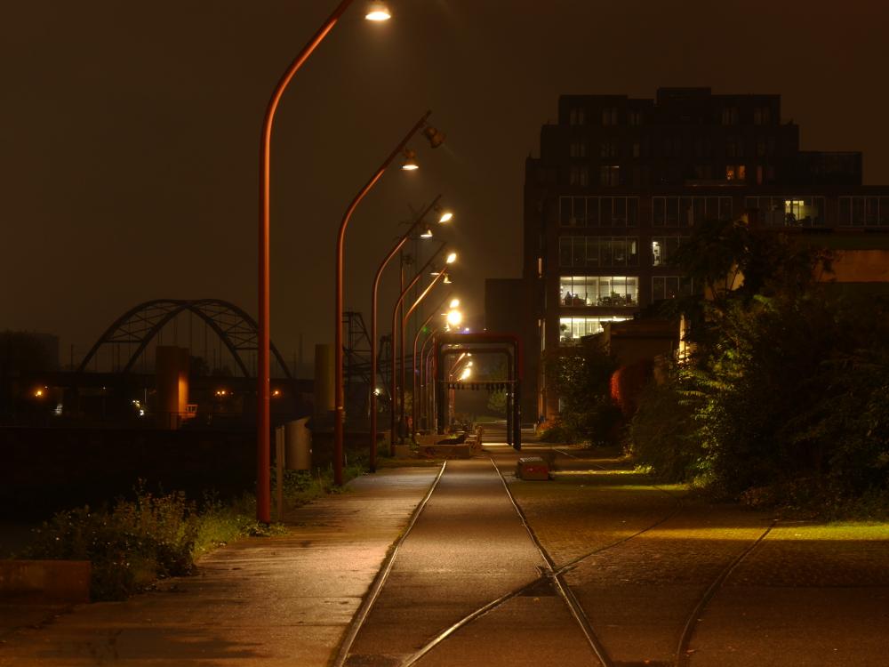 Das Foto zeigt den heutigen Fußweg am Verbindungskanal in Mannheim-Jungbusch, man sieht noch die alten, heute einbetonierten Schienen.