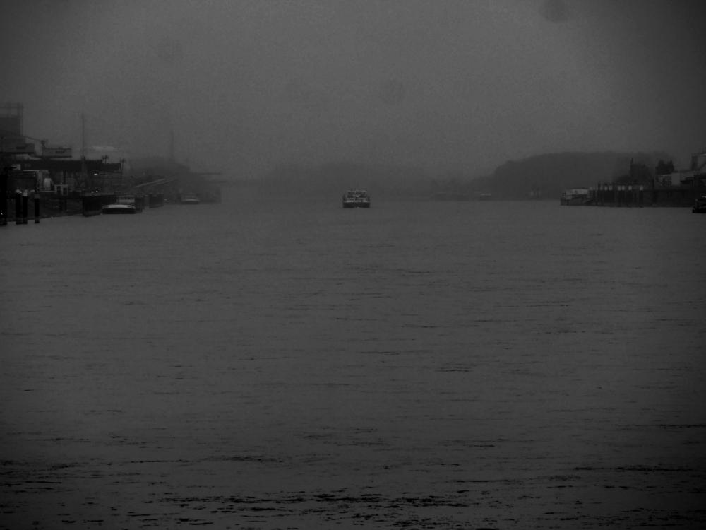 """Das s/w-Foto zeigt den Rhein, der im Nebel """"verschwindet"""". Auf dem Rhein fährt kurz vor dem Nebel ein Schiff, Rechts und Links kann man Industiregebiete erkennen."""