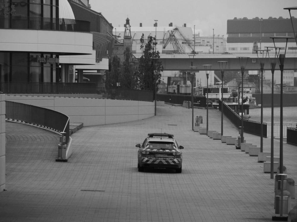 Das s/w-Foto zeigt einen Streifenwagen der Polizei auf der Rheinpromenande in Ludwigshafen kurz vor der Rheingalerie