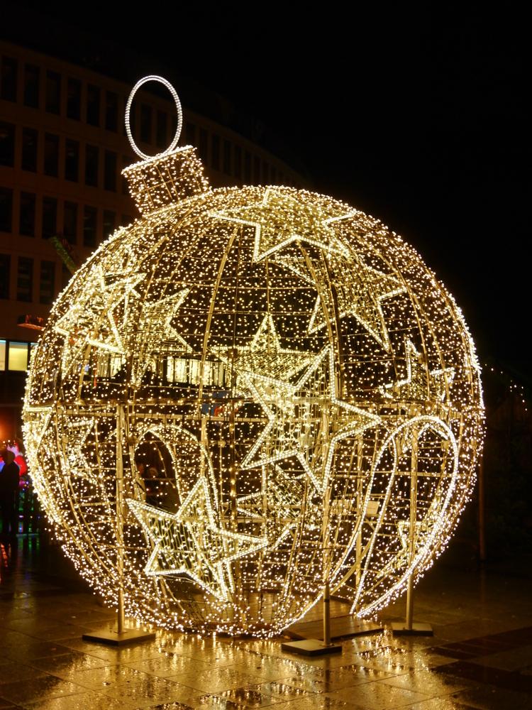 Das Foto zeigt eine überdimensionale, behgehbare Christbaumkugel, die aus LIchterketten besteht.