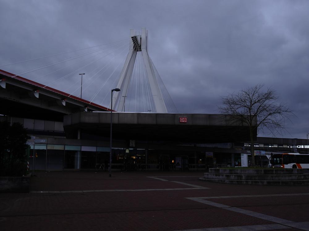 Das Foto zeigt den Hauptbahnhof von Ludwigshafen, ein graues Betongebäude. Über dem Bahnhof ist eine Autobahnbrücke.