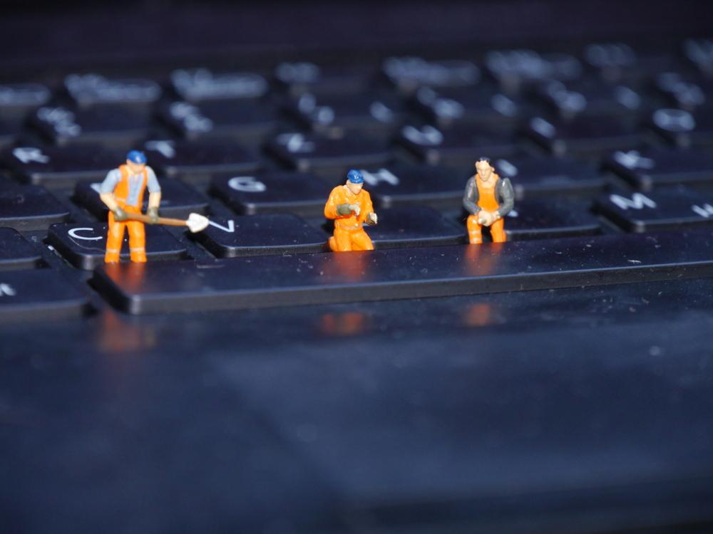 """Dasa Foto zeigt Modell-Bauarbeiter in Warnkleidung, die auf der Tastatur eines Computers """"arbeiten""""."""