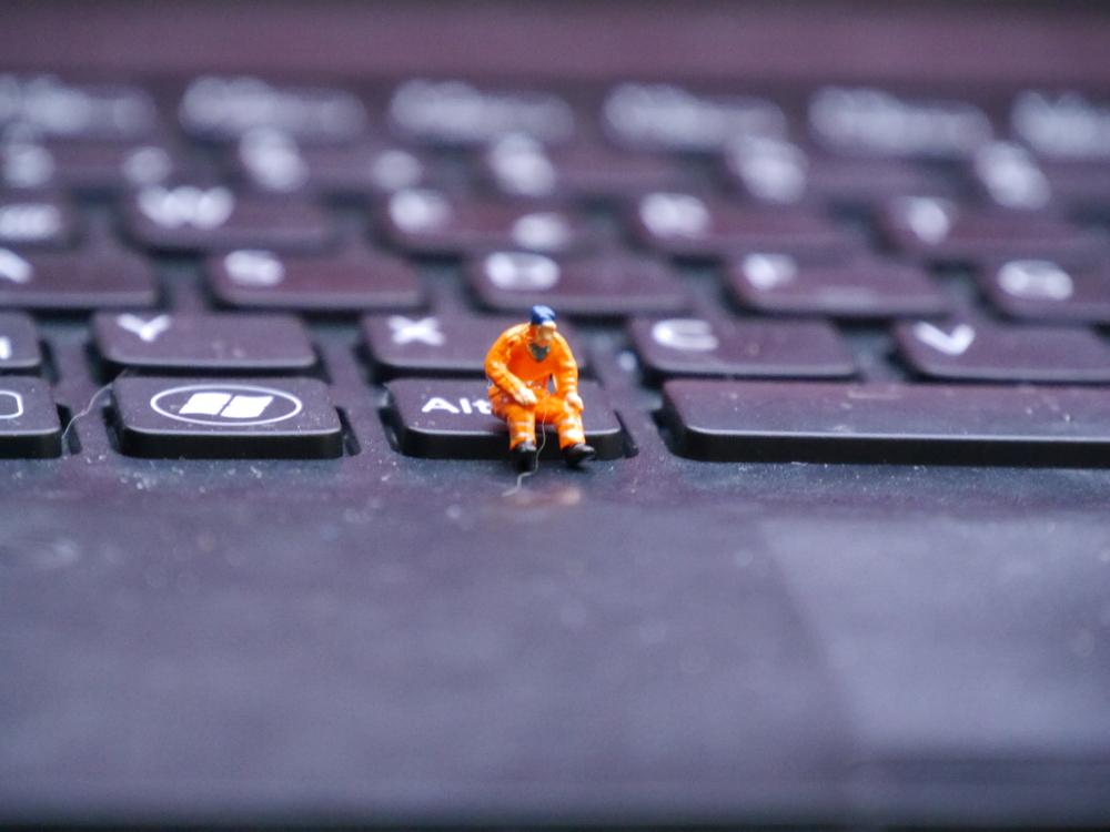 Das Foto zeigt einen Modell-Bauarbeiter, der in Warnkleidung auf der Alt-Taste eines Computers sitzt