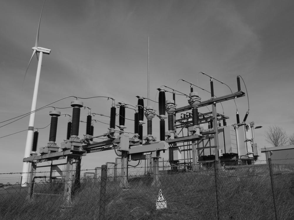 Das s/W-Foto zeigt eine kleine Trafostation, daneben eine Windkraftanlage
