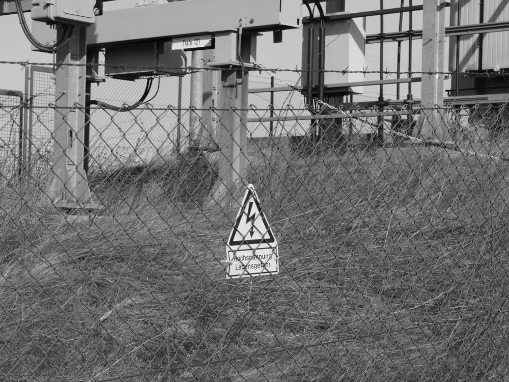 """Dasa Foto zeigt ein """"Hochspannung, Lebensgefahr!"""" Schild am Zaun der Trafostation"""